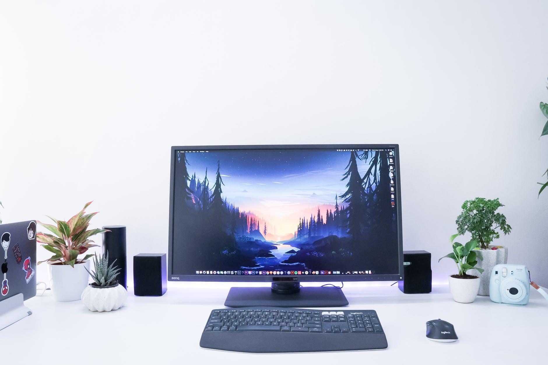monitor z klawiaturą i myszką na białym biurku